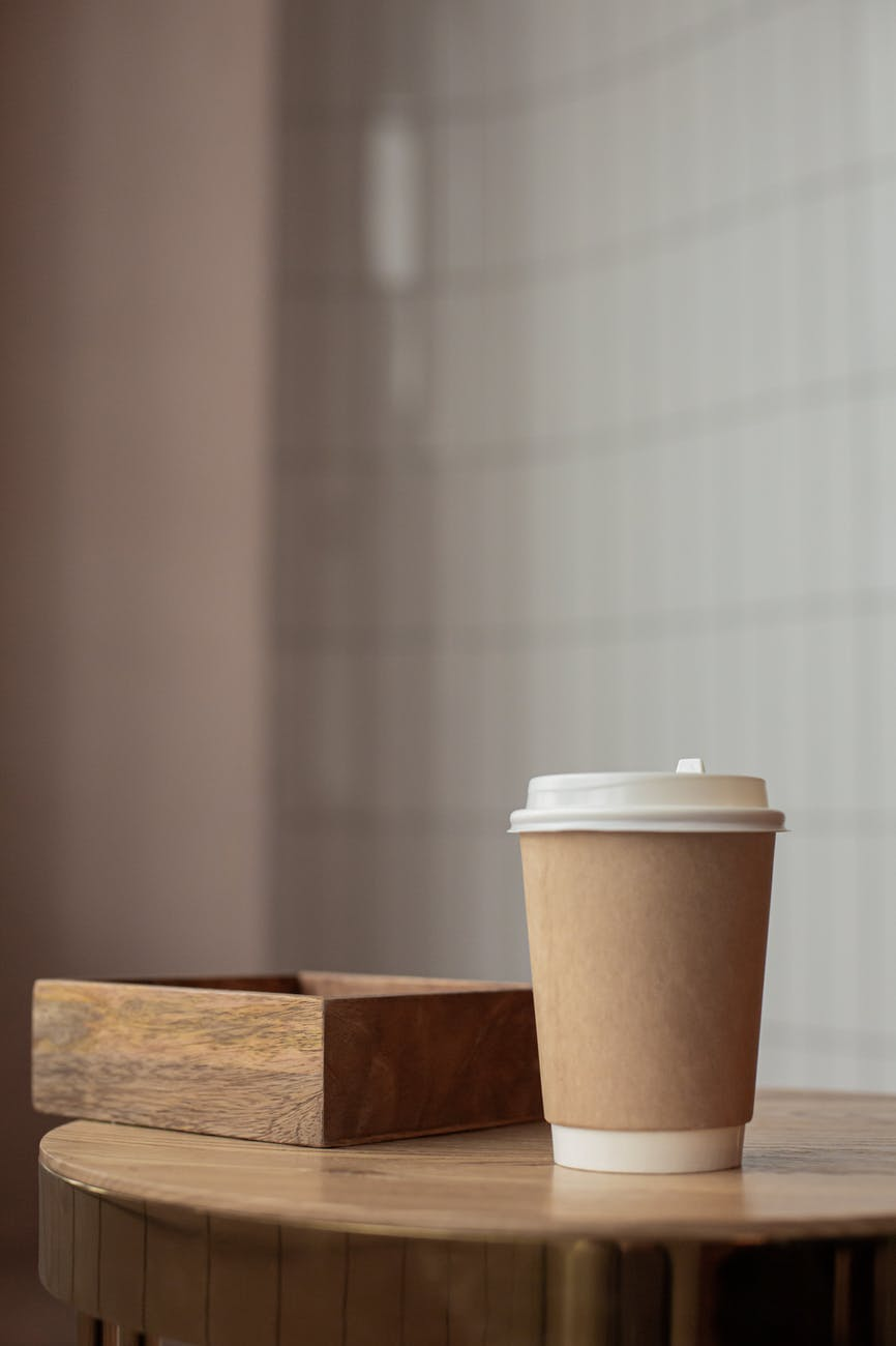 a coffee cup and a wooden box tray on a table