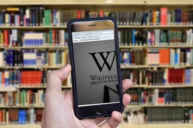 Wikipedia on a mobile in front of book shelves