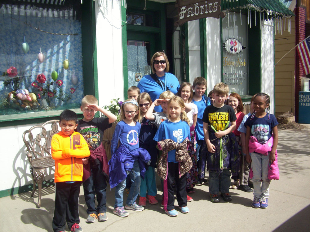 Mrs. Good poses with her class outside the store.