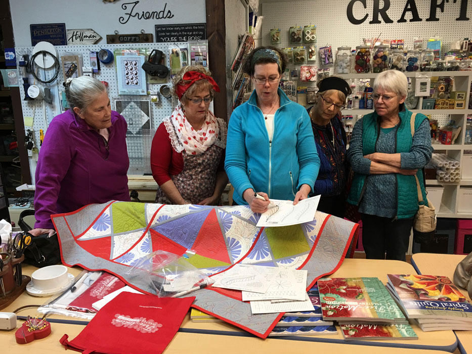 ReNae Merrill demonstartes the process to several Fabric Nook customers.