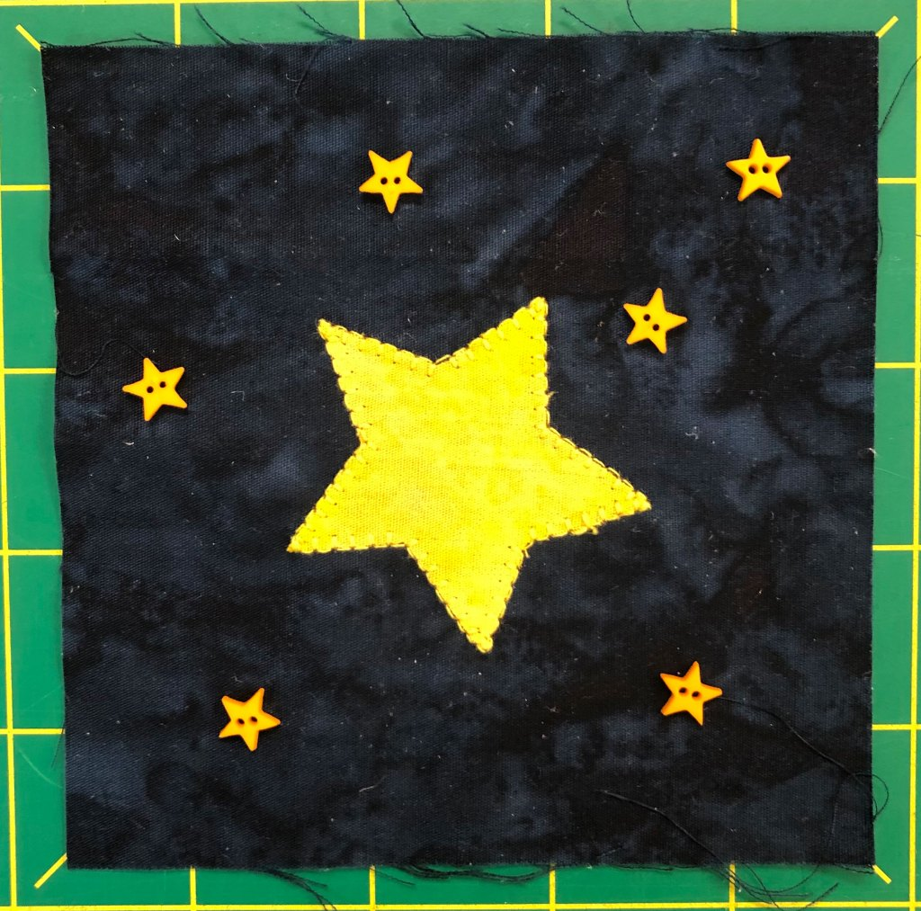Fabric quilt block of stars with a big star in the middle.