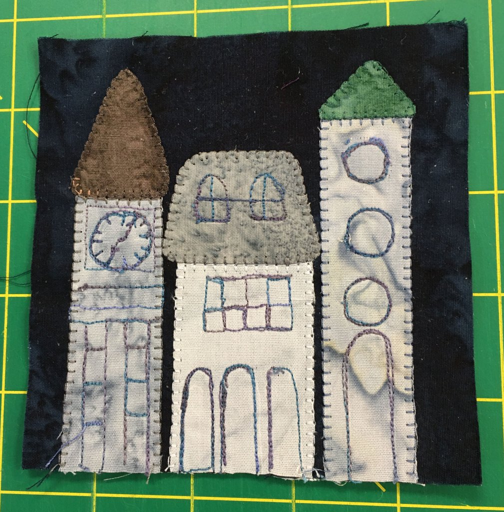 A quilt block featuring three buildings in a row. One is tall with a clock at the top, and the far right building has large round windows.