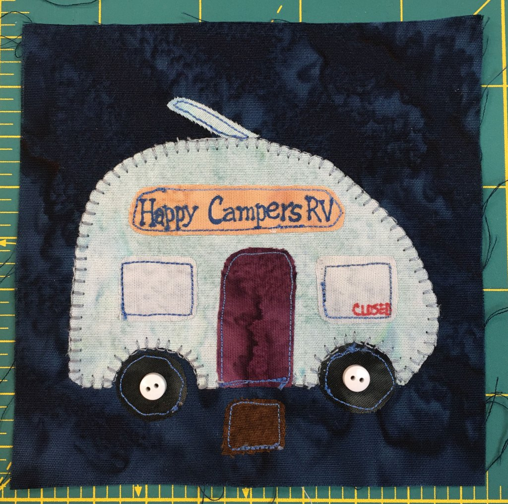 """This quilt block shows an RV camper with a sign on it reading, """"Happy Campers RV."""" There is a window on the right that reads, """"Closed."""""""