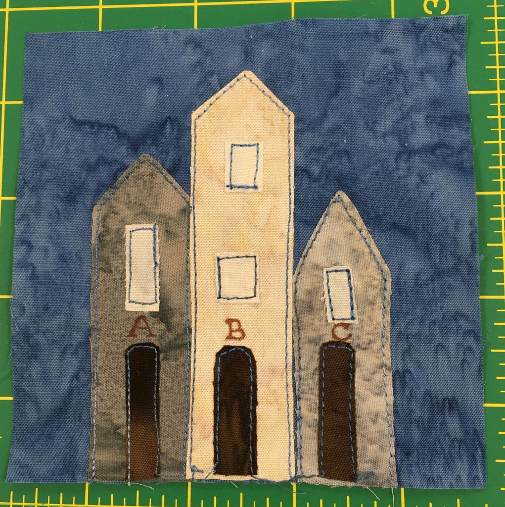 This quilt block shows three tall buildings with pointy roofs. The middle lighter one is two stories tall. They are labeld above the dark doors with the letters A, B, and C.