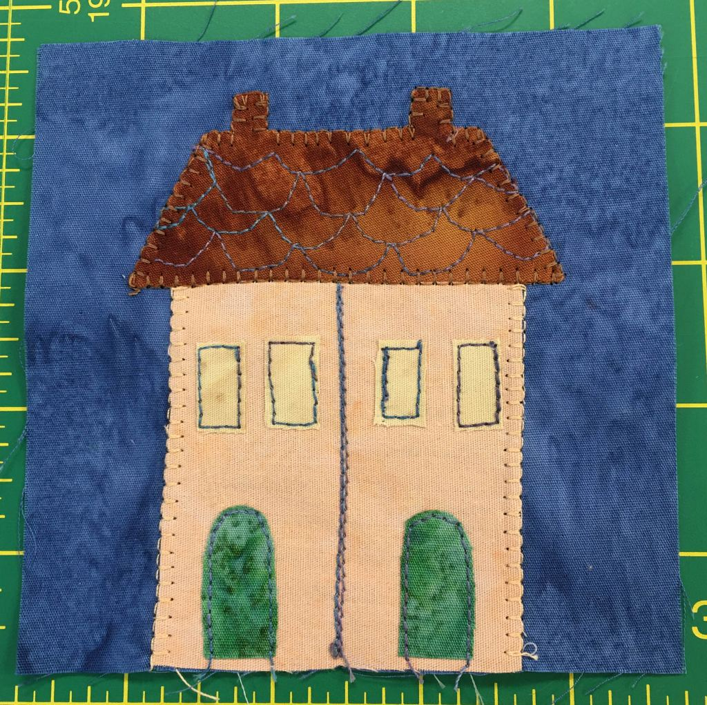 This quilt block features a house that is split down the middle. It has a shared roof with two chimneys, but there's a lien down the midle of the building's body and two green doors with two sets of windows.