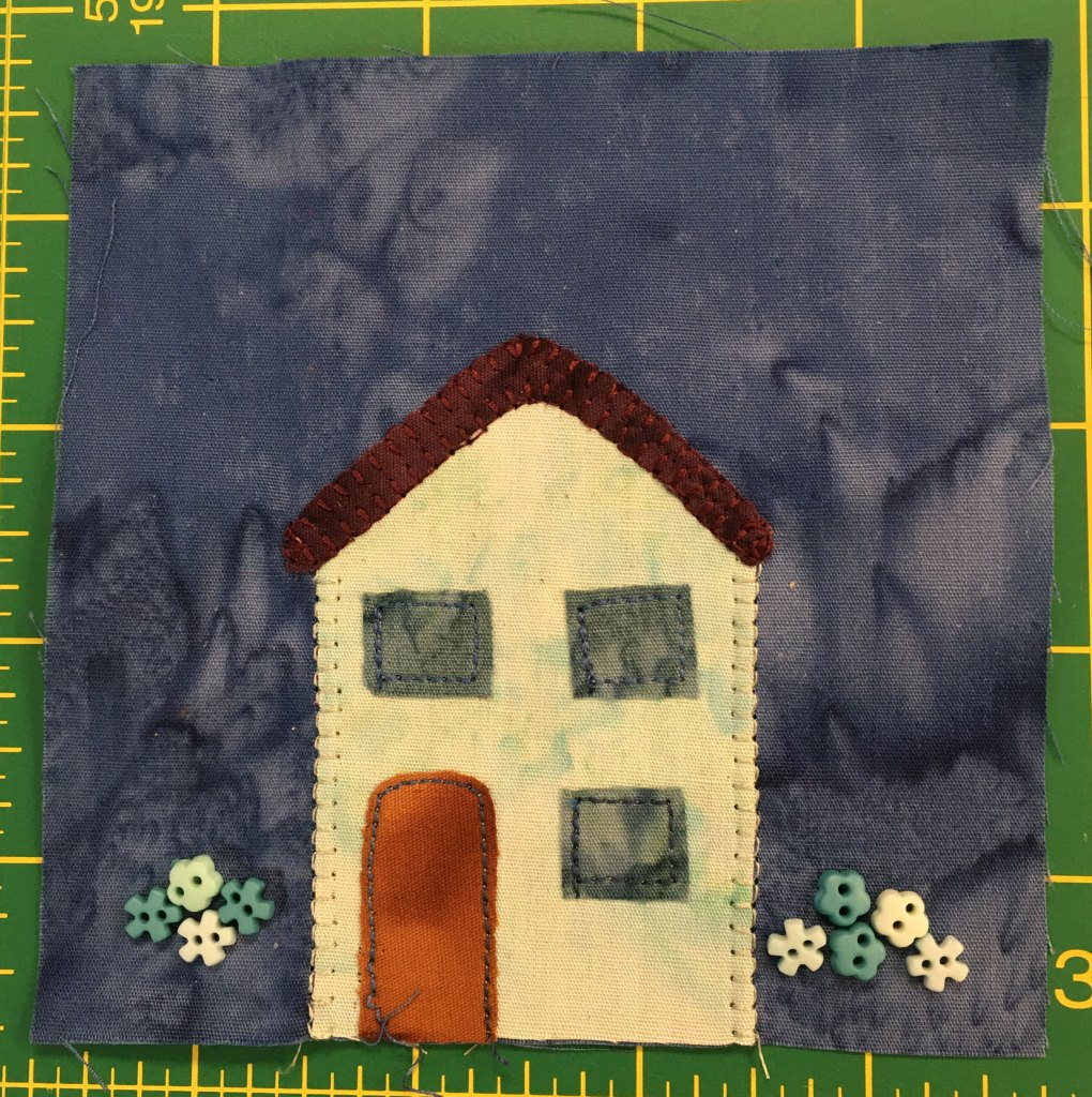 This quilt block shows a straight forward house with three windows and a red door. The house is off white. Next to the house are buttons showing flower blossoms.