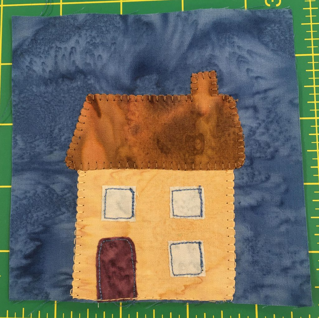 This block shows a simple two story yellow house with three square windows, one below and two above. There is a maroon door on the left, and a brown roof with a chimney on the right.