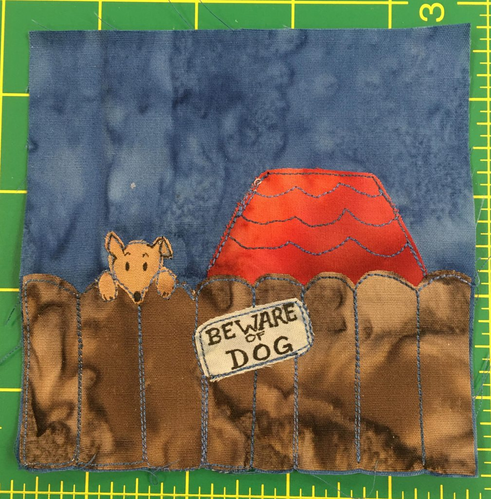 """This quilt block shows a brown fence in front of a house. You can only see the red roof of the house. On the fence is a sign that says, """"Beware Of Dog."""" On the left side of the fence, above it, is a dog's head poking over looking at the viewer innocently,"""