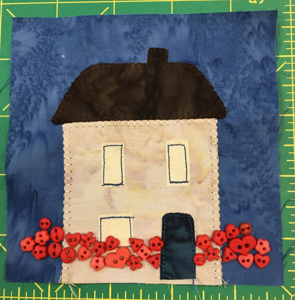This quilt block shows a tall square house with a dark roof and a chimney. There are two floors with three windows and a dark door. All along the bottom of the square are small red buttons in various little shapes, including hearts, to signify flowers.
