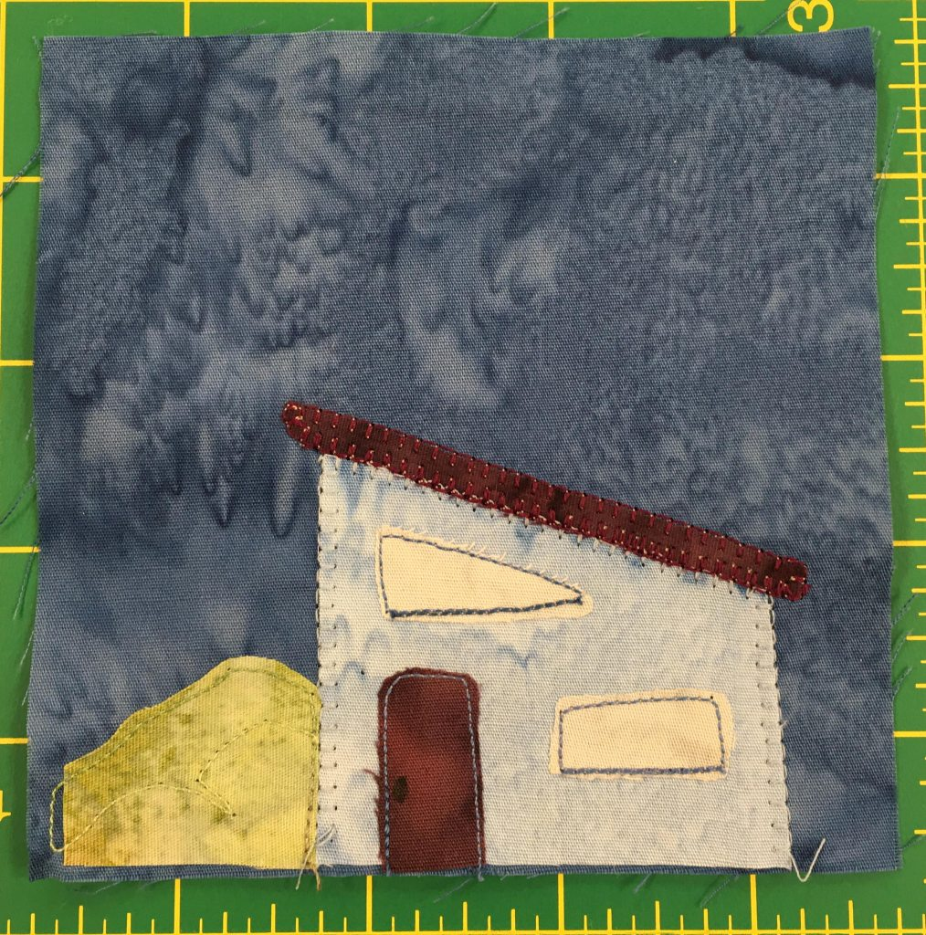 This quilt block shows a gray house with a slanted roof that slopes downward to the right. The house has a second-floor window that's in the shape of a triangle.To the left of the house is a green bush like might be found in a suburban yard.