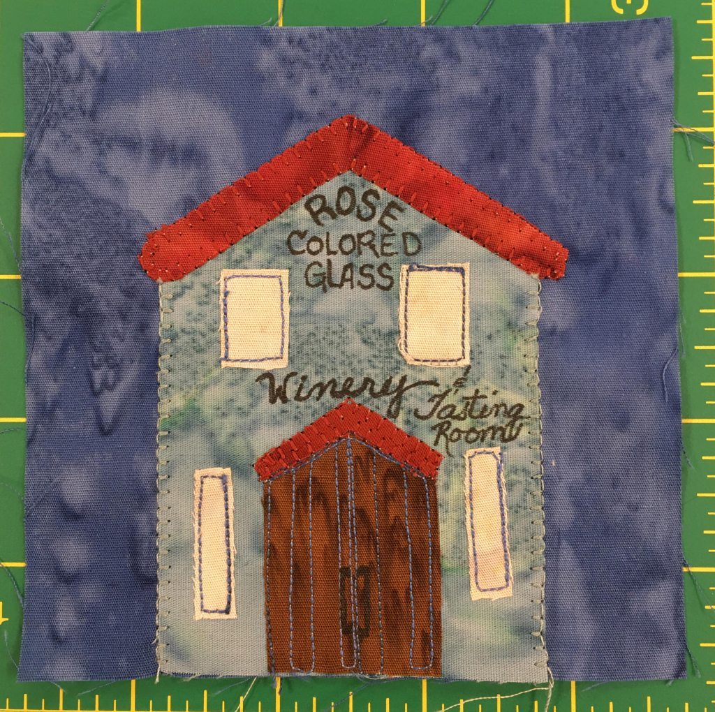 """This quilt block shows a tall gray-blue building with a red triangular roof. There are two windows on the second floor and two tall windows on the first floor next to a set of arched double doors. On the building are the words, """"Rose Colored Glass, Winery and Tasing Room"""""""
