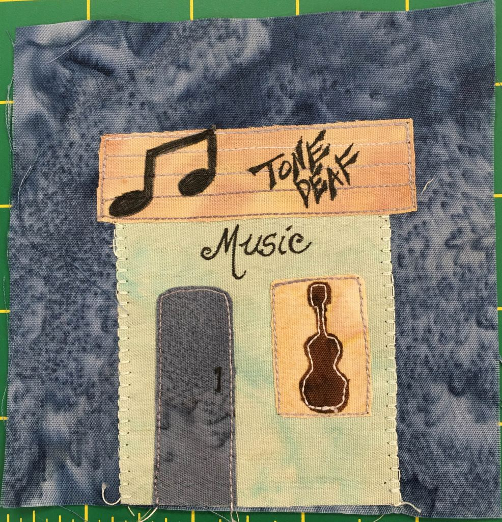 """This quilt block shows a square building with a flat rectangular roof. On the roof like a static marquee with a logo on it are the words, """"Tone Deaf."""" It's amusic store. There are musical notes next ot eh wrods, and the image of a guitar on the window on the right side of the builidng."""