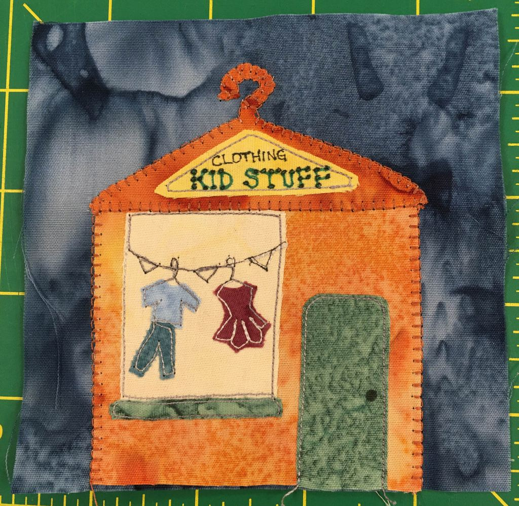 "This quilt block shows an orange building with a coat hanger shaped roof. On the roof a triangular sign reads ""Clothing, Kid Stuff."" In the display windows on the left is a clothesline with a boy's and girl's outfit hanging from it."