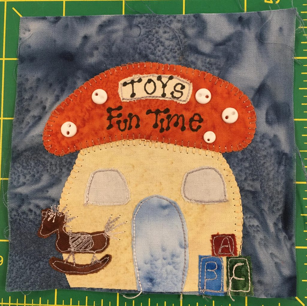"""This quilt block shows a mushroom shaped building with an orange polka-dotted top. The polka-dots are made with little light two-holed buttons. On the cap roof it reads, """"Toys, Fun Time."""" In front of the main mushroom stalk is a wooden rocking horse and a set of blocks."""