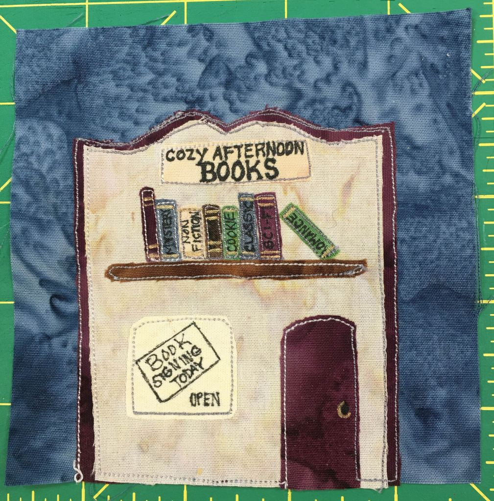 """This quilt block shows a store front of a bookstore. The building's decorative roof is shaped in such a way that it makes the building look like an open book. Under the roof lining is a sign that says, """"Cozy Afternoon Books."""" Underneath that is a picture of several volumes of books of different colors on a shelf, each with a title that is a major genre, such as non-fiction, classic, sci-fi, and romance. Underneath that is a maroon door, and a sign that has a paper up that reads, """"Book Signing Today, Open."""""""