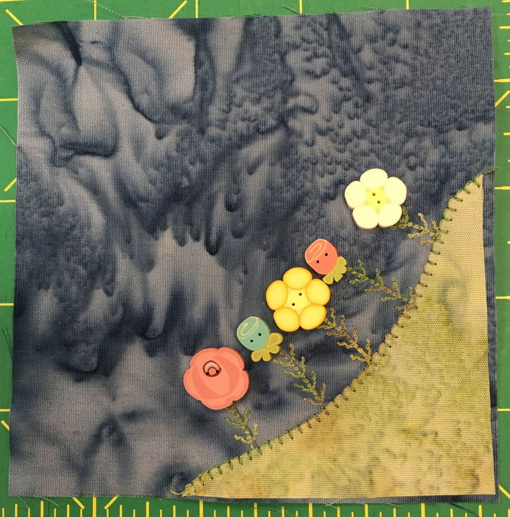This quilt block shows a corner block with a patch of grass in the lower right corner. Poking out of the grass and towards the center of the block are several very detailed flowers of various kinds and colors. The detail of each flower bloom stands out in this block; the blooms themselves being medium sized flower pattern buttons.