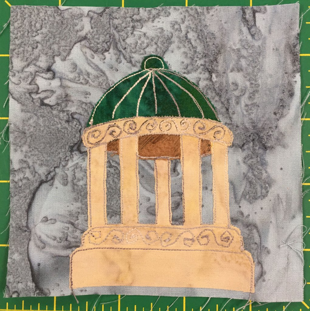 This quilt block shows a round gazebo or rotunda like structure with a base, columns, and a green dome top. The green dome top has white stitching on it cutting it into sections and a ball at the top of the dome. The columns are all in a circle supporting the dome, and below and above the columns is additional stone with decoration or etchings into the stone. The stone itself is a light yellow. The whole thing is very classically Greek like.