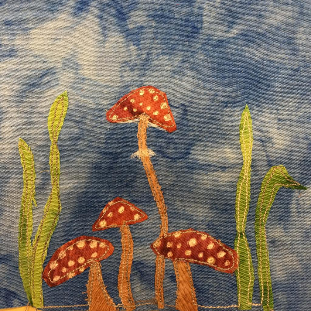 This quilt block shows four toadstools. These are the standard psychoactive toadstools featured everywhere, with orange stalks, red tops, and white spots. One toadstool is much taller and thinner than the others. There are also two stalks of grass and on either side of the toadstools.
