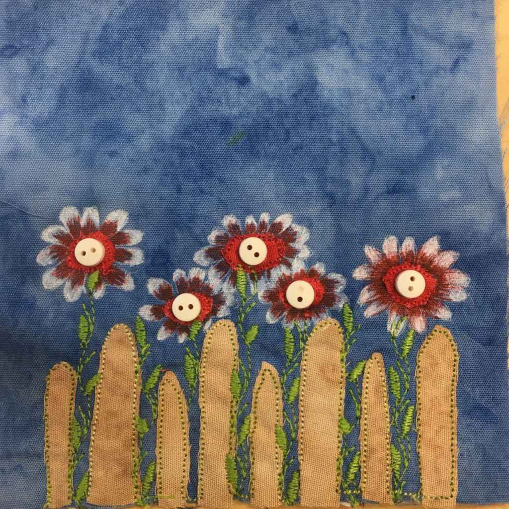 This quilt block shows a tan fence with slats that have significant gaps between them. The slats are rounded at the end. In between the slats and above them are a row of beautiful flowers. The greenery for the flowers is done with intricate stitching, with even the leaves as stitches. The flowers are a combination of red fabric with medium sized two-hole buttons in the center, and red and white pen marking coming out from the center to show beautiful flower petals. This is all against a blue salmon-patterned background.