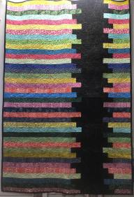 A large quilt made with a jelly roll (or more). It features a black jagged stripe on the left side going down, and horizontally many multi-colored stripes.