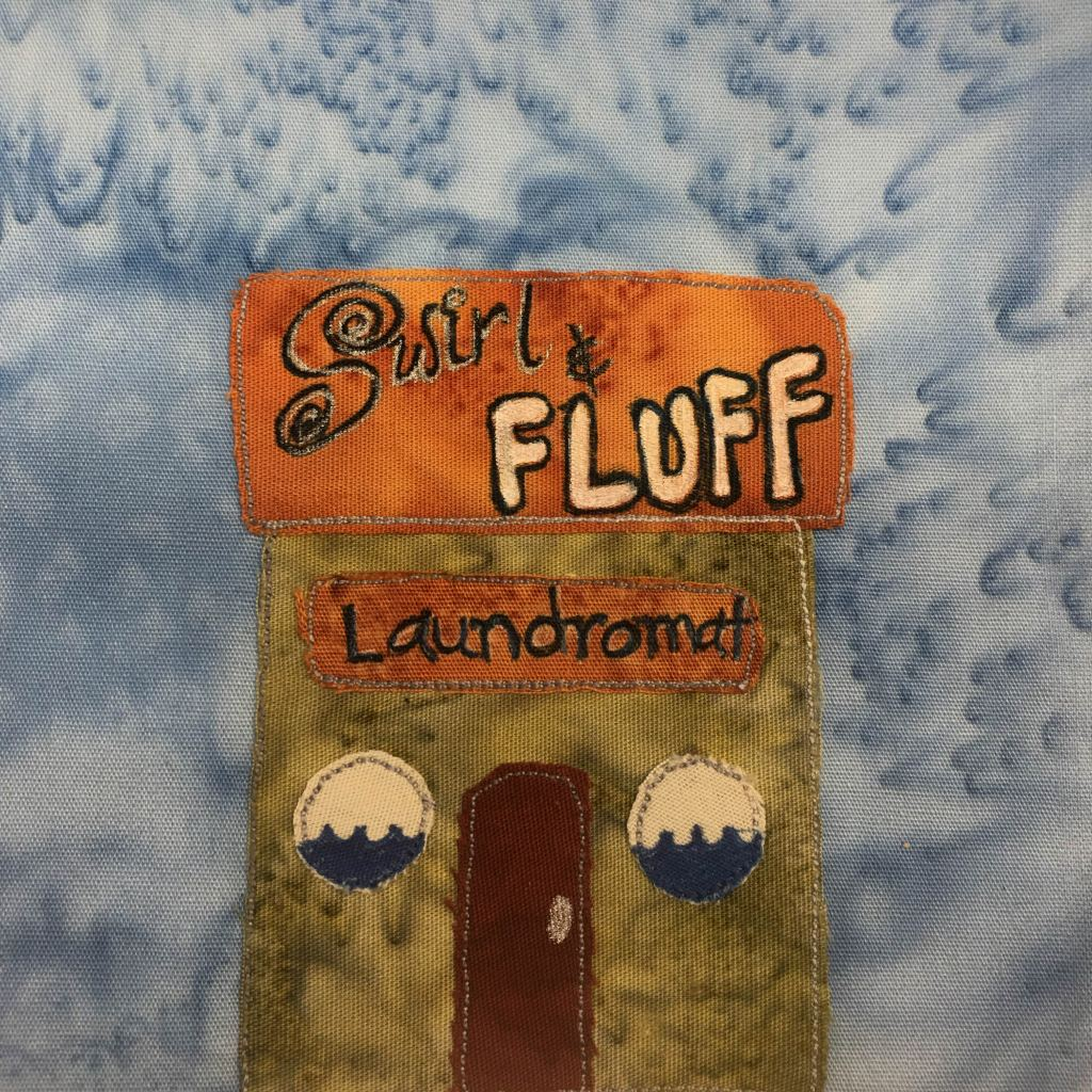 """This quilt block shows a square building with a square flat roof. The roof is orange with the words, """"Swirl & Fluff"""" written on it. The swirl is in black and white pen, and the S has swirls on it. The fluff is in bold white with black pen outlines. Below the orange roof is a green building with a darker orange sign on it that reads, """"Laundromat."""" The windows on either side of the red door are round. They each have waves of water on the bottom half, as if one is looking into a washing machine. The door is red and in the center."""