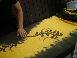 Artiste indonésien faisant une démonstration de batik lors des atelier de l'ISEND à Kuching, après l'application de la cire chaude au pinceau, il vaporisait des teintures d'autres couleurs sur la toile tendue entre deux poteaux
