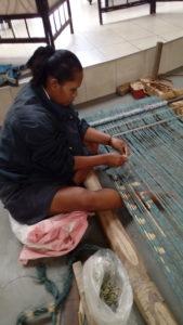 Elimination des liens de réserve sur une chaîne d'ikat en raphia teinte à l'indigo, à l'Alliance Française d'Antananarivo