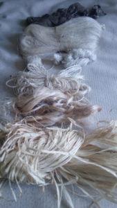 Différentes fibres, de haut en bas, soie sauvage, soie domestique non décreusée, soie décreusées (fibres animales), puis sisal, fibre de bananier et raphia de Madagascar