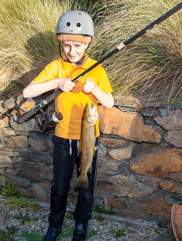 Young boy holding a large brown trout at Tin Dragon Cottages