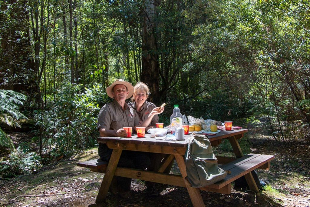 Man and woman sitting at a picnic table in a bush setting