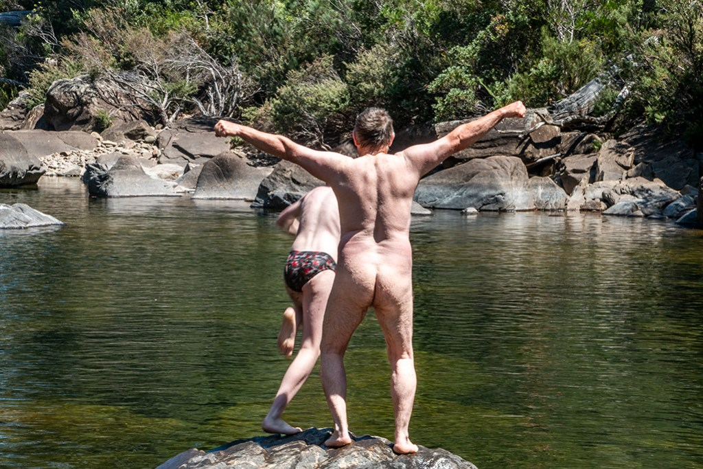 Naked man on a rock above a deep rock pool - back only. A boy just diving into the water near by.