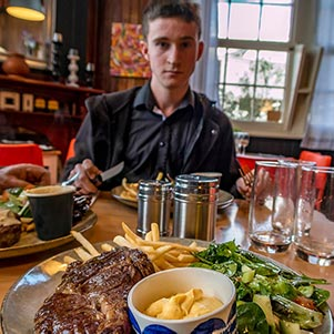 James eating a meal of steak chips and salad at a local hotel