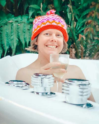 A lady wearing a red beanie is  sitting in an outdoor spa holding a glass of white wine. The outdoor spa at Tin Dragon Cottages is a special feature of a North East Tasmania itinerary.