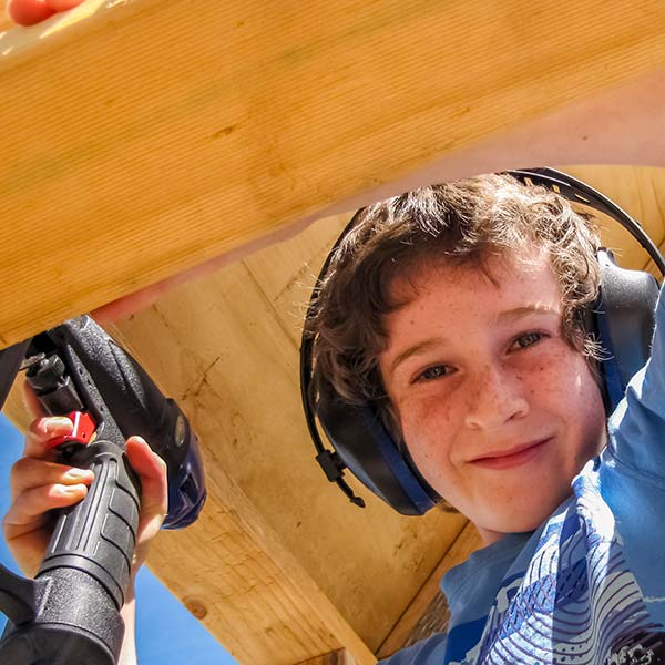 A young boy holding a battery drill and wearing ear protection is on site at the hydro generator shed build.