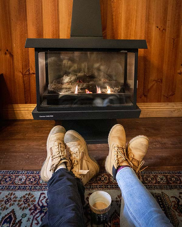 A young couple is sitting on the floor in front of a gas fire sharing a cup of hot chocolate.
