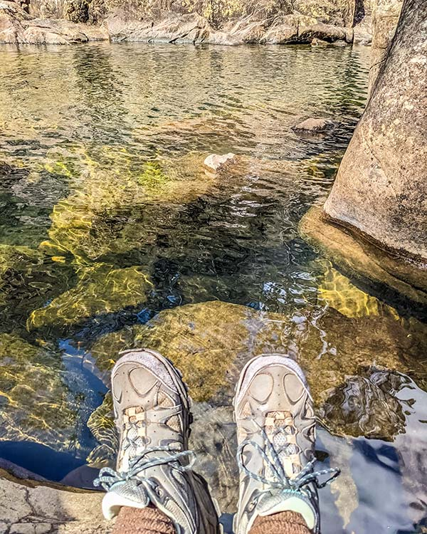At the water's edge are my feet. The water is very clear and reveals the rocks beneath.