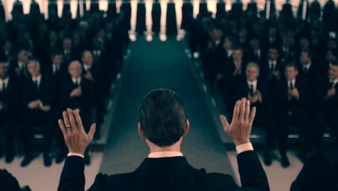 General de costas e uma multidão de homens sentados.