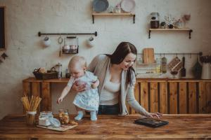 Mom and daughter playing together with tablet in home interior lifestyle real