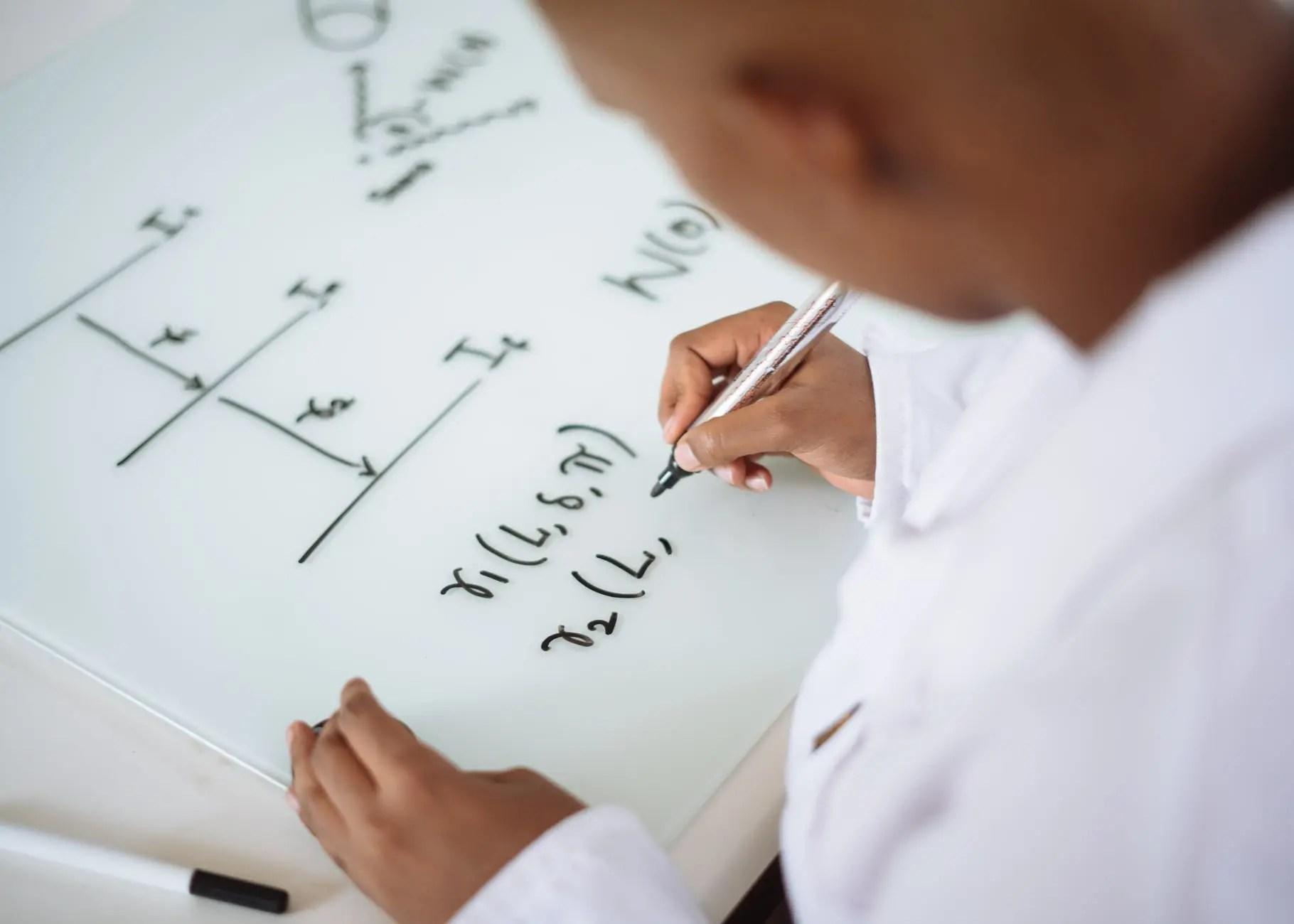 photo of person deriving formula on white board