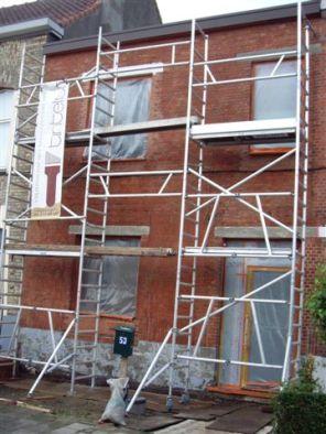 Gevel in stelling. Ramen, vensterbanken, grond en deuren afgeplakt.