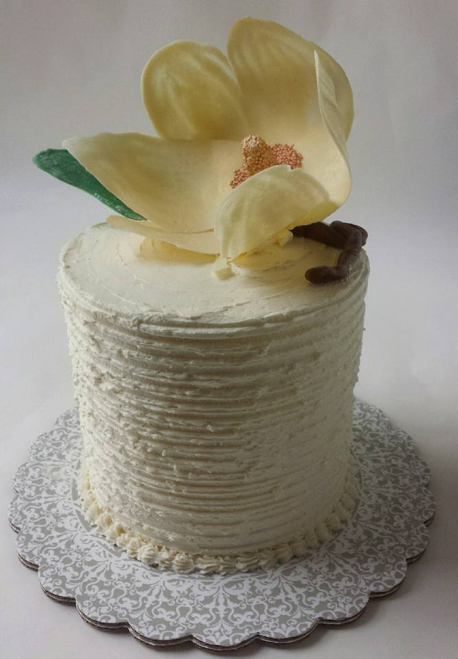 Lemon buttercream frosted lemon curd birthday cake with large chocolate magnolia blossom decoration.