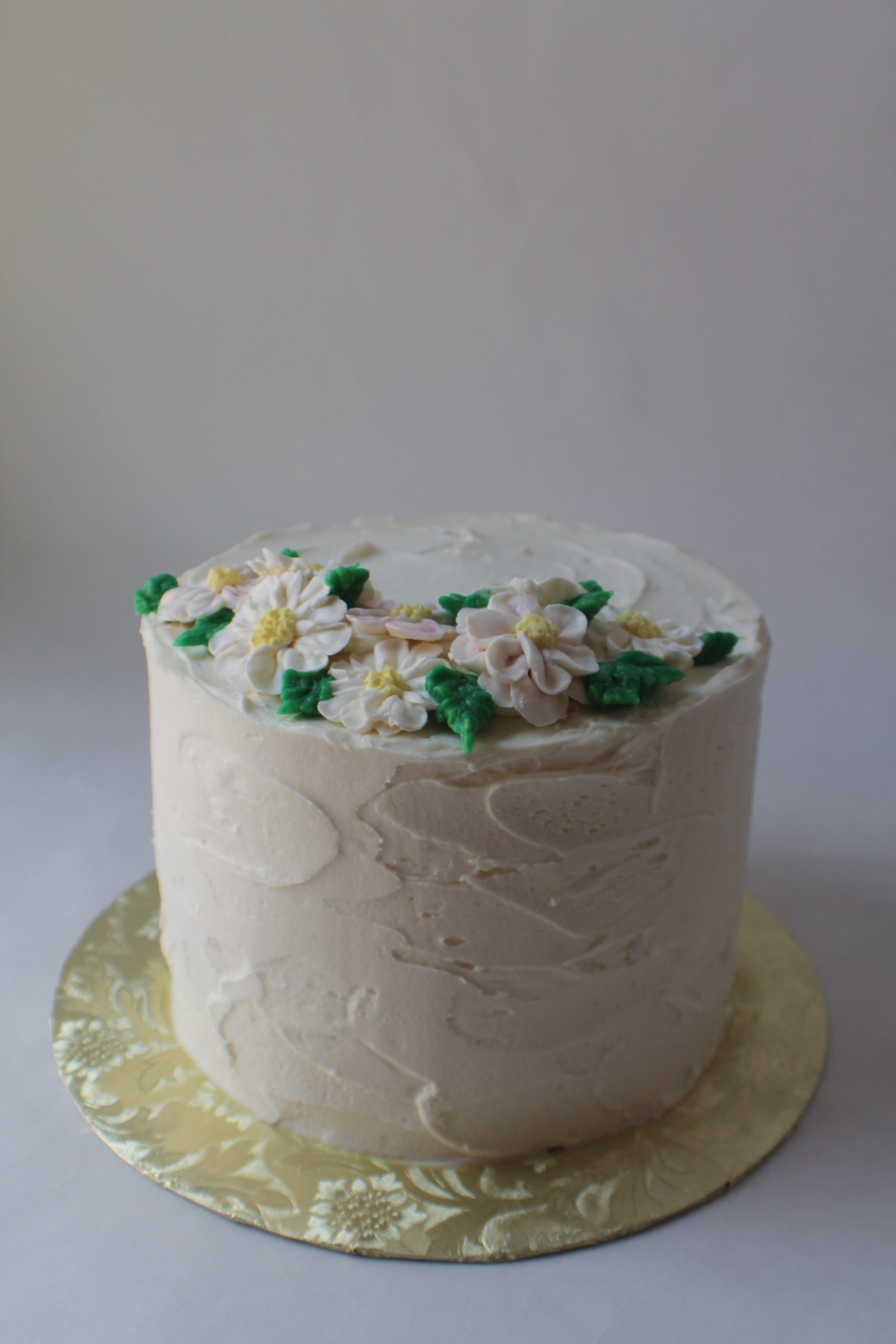 Vanilla buttercream frosted cake with buttercream daisies