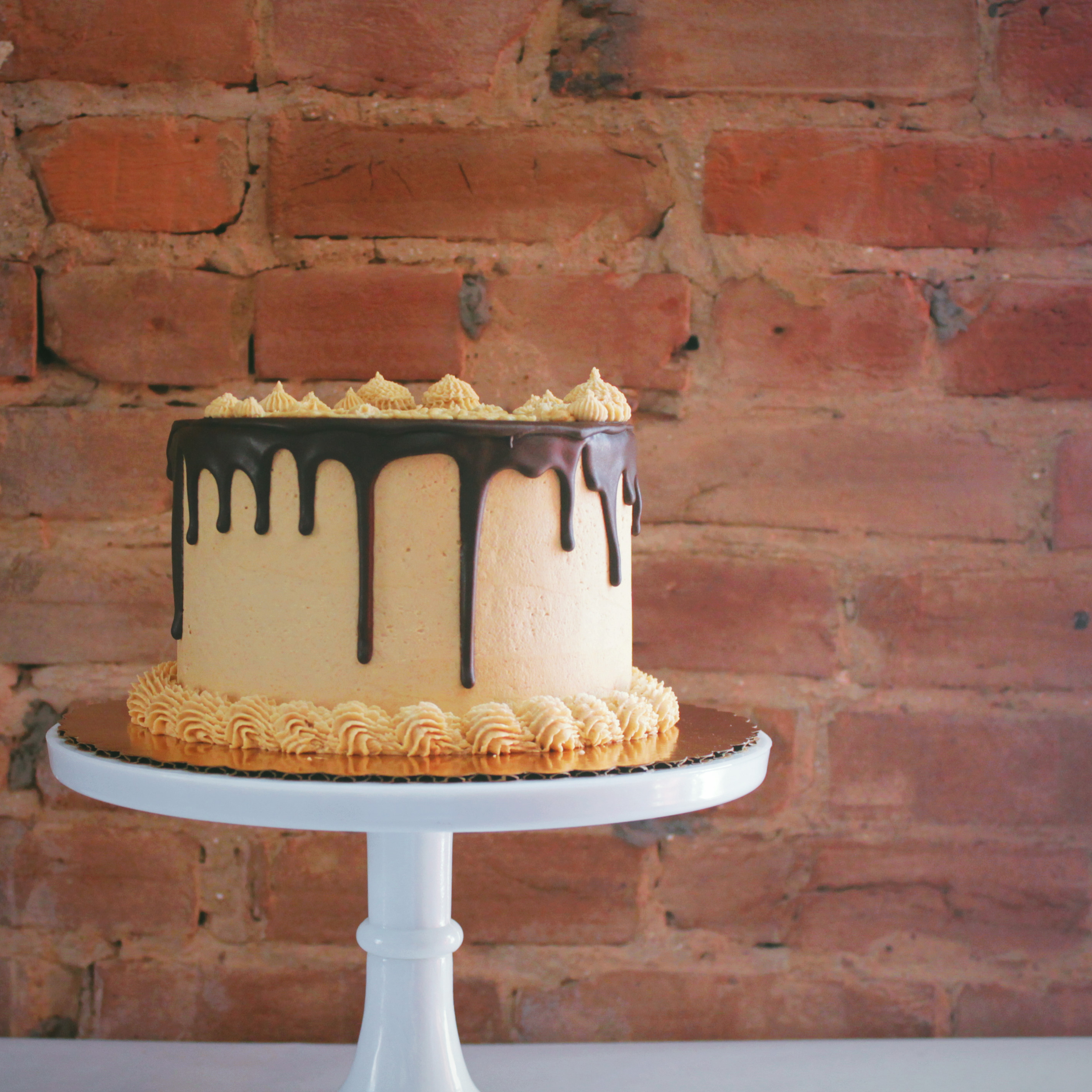 Chocolate cake with peanut butter buttercream frosting and a chocolate glaze drip.