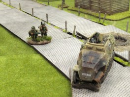 A Para PIAT team bravely sets up in open ground to get a clear shot down the road...