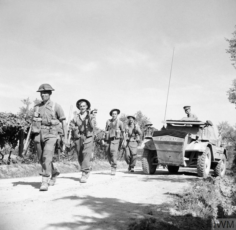 THE BRITISH ARMY IN ITALY 1944 (NA 16556) British Infantry move up past a Daimler scout car during the advance of 78th Division, 30 June 1944. Copyright: © IWM. Original Source: http://www.iwm.org.uk/collections/item/object/205204664
