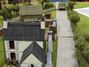 HE rounds slam into the white farmhouse, rattling the Brit infantry inside