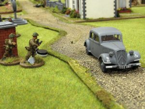 Suppression markers on the Bren team, while the boss hoofs it past them in his Citroen.