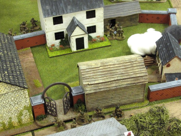British troops surround the remaining Germans in the white farmhouse
