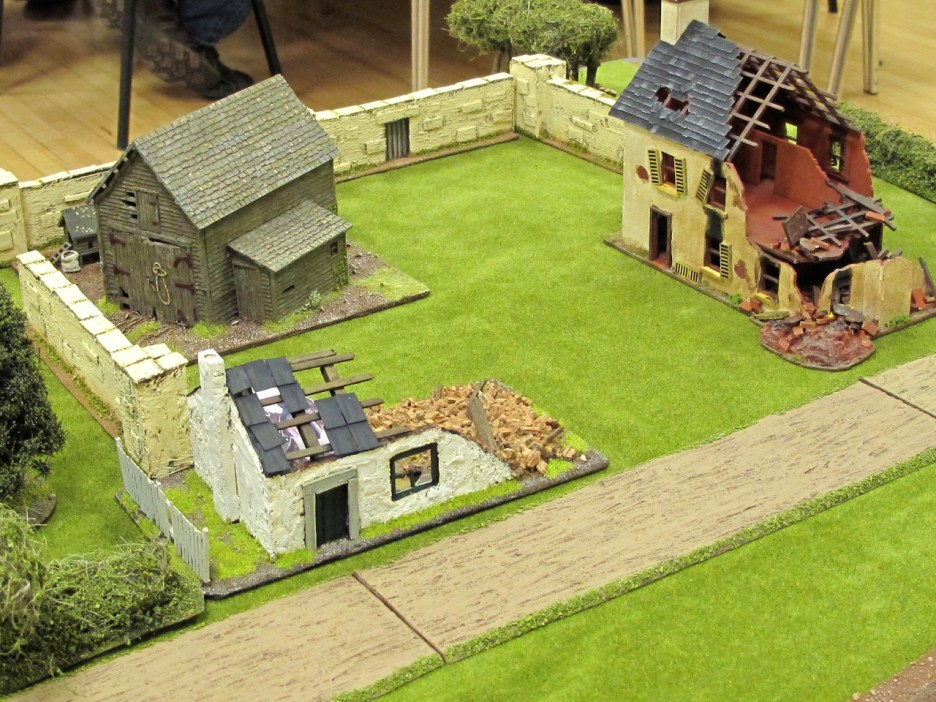 The farm was pretty much demolished by the Royal Engineers in the previous game. Both stone buildings are in ruins, and the surrounding wall has been breached.