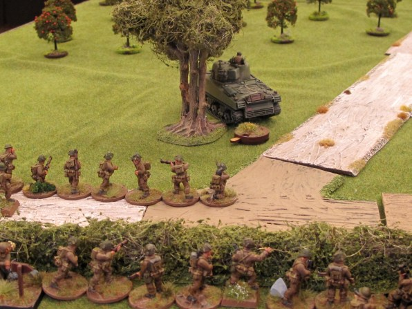 Rattled but not defeated the Sherman parks up for a breather while an infantry section moves up to join it.